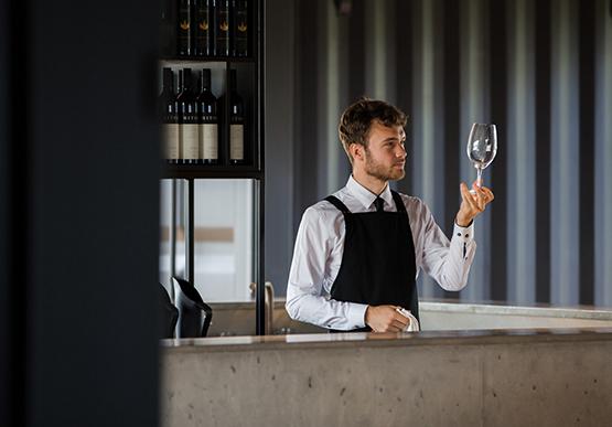 Man working behind bar at winery.